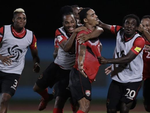 Photo: Trinidad and Tobago right-back Alvin Jones (third from left) celebrates with teammates after his stunning goal against the United States during 2018 World Cup qualifying action in Couva on 10 October 2017. (Copyright AFP 2017/Luis Acosta)