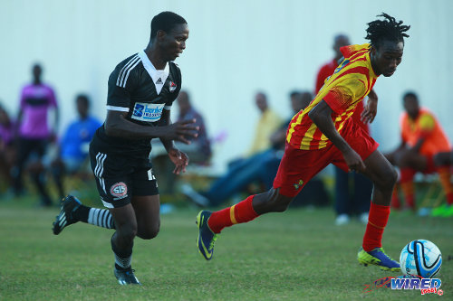 Photo: Point Fortin Civic midfielder Akeem Redhead (right) takes Central FC wing back Kaydion Gabriel for a run during the 2014/15 season. (Courtesy Allan V Crane/Wired868)