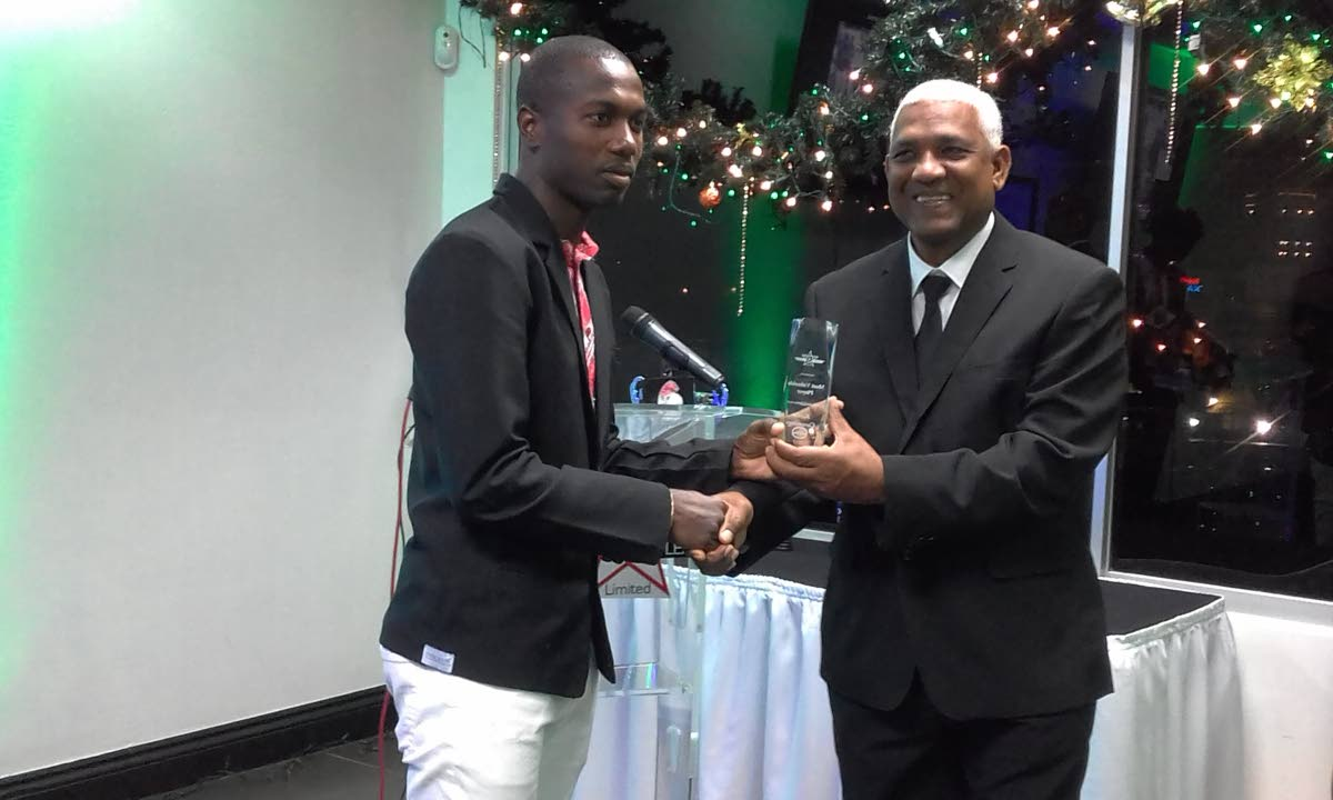 Keron Cummings, left, receives his League Two Super League MVP trophy from League second vice-president Edison Dean.