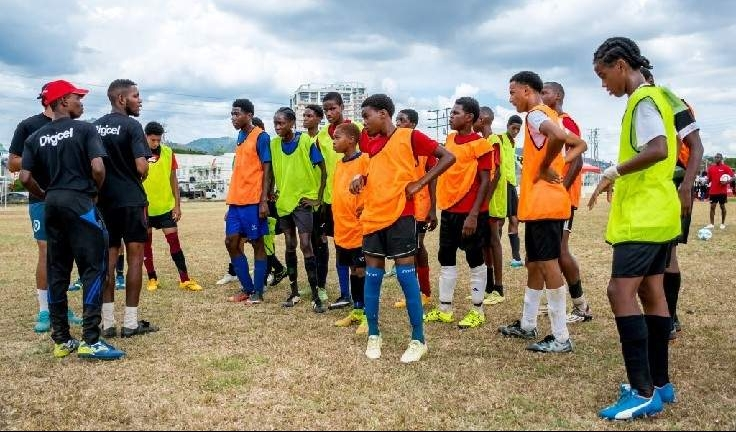 Players chosen from the Trinidad end of the Digicel Kickstart pre-selection clinic listen to instructions from their coaches at the Fatima College ground.