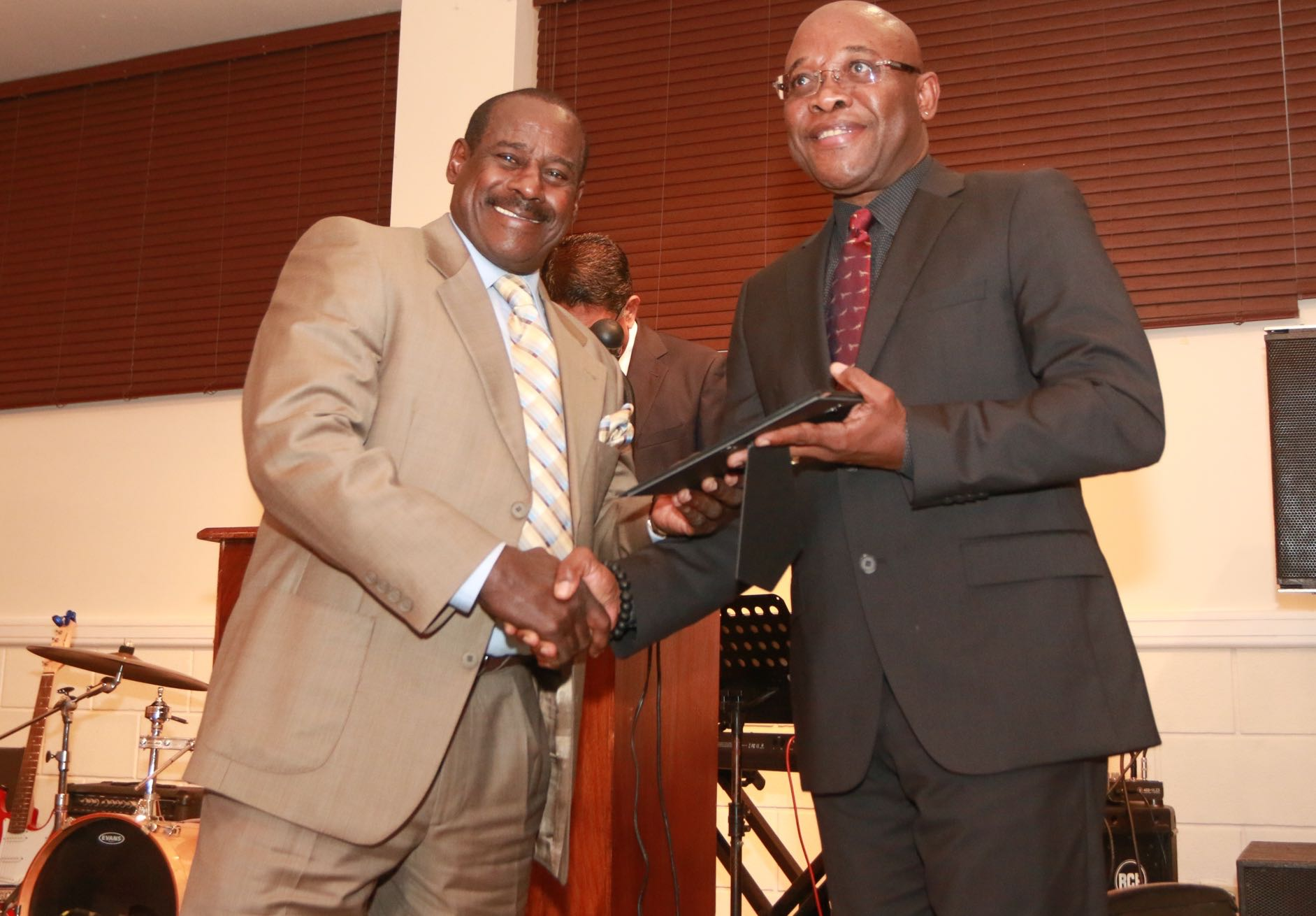 Everald Cummings receives his award from NLCB Chairman Marvin Johncilla at a TTFA Dinner on the visit of the FIFA President Gianni Infantino last Monday.