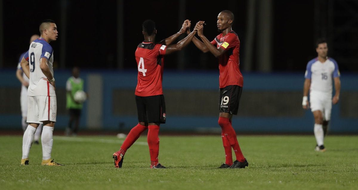 Trinidad and Tobago's Kevan George, center right, and Kevon Villaroel celebrate as the U.S.'s Bobby Wood, left, looks on after their World Cup qualifying match at Ato Boldon Stadium in Couva, Trinidad and Tobago, Tuesday, Oct. 10, 2017. (AP Photo/Rebecca Blackwell) — with Kev Villaroel and Kevan George at Ato Boldon Stadium.