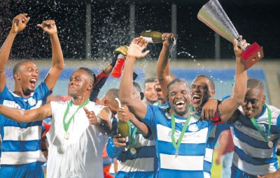 Captain of Guaya United Glenton Wolfe, holding trophy, celebrates with head coach Ron La Forest, second from left, and the rest of their team, following their 3-1 win over Prisons FC in the finals of the TTSL's CFTL League Cup at the Ato Boldon Stadium, Couva.