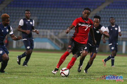Photo: Trinidad and Tobago National Under-20 winger Isaiah Hudson (centre) runs at the Turks and Caicos defence during Caribbean Cup qualifying action at the Ato Boldon Stadium on 17 June 2016. T&T won 11-0.... (Courtesy Chevaughn Christopher/Wired868)