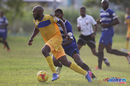 Photo: FC Santa Rosa captain Keron Clarke (left) looks to escape from a WASA FC opponent during TTSL One action in St Joseph on 9 July 2017. Clarke scored twice as Rosa won 3-0. ...(Courtesy Chevaughn Christopher/Wired868)