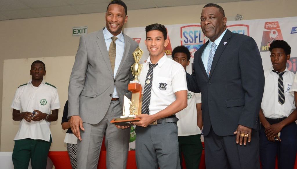 "Shaka Hislop, left, and president of SSFL William Wallace present the boys' ""Player of the Year"" trophy to Mark Ramdeen of Naparima College during the awards function, yesterday."
