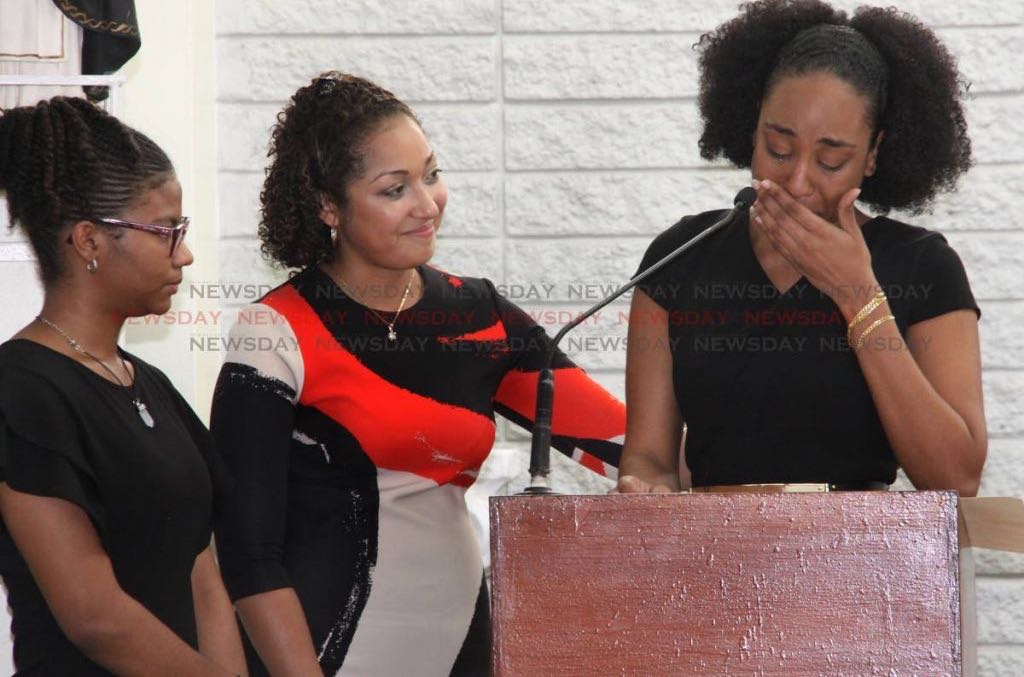 Myca-Lee Mc Comie, right,weeps at the funeral of her father, Michael McComie, at Holy Cross Chapel, Calvary Hill, Arima.
