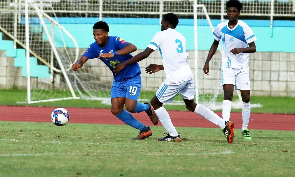 Naparima College's Decklan Marcelle(10) evades two La Romaine players during action in the South Zone, Secondary Schools Intercol quarterfinal match, at the Manny Ramjohn Stadium,Marabella, yesterday.