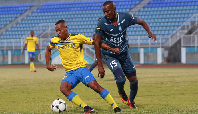 ​Police FC forward Jameel Perry (right) pictured in this file photo as Defence Force defender Curtis Gonzales shields the ball.
