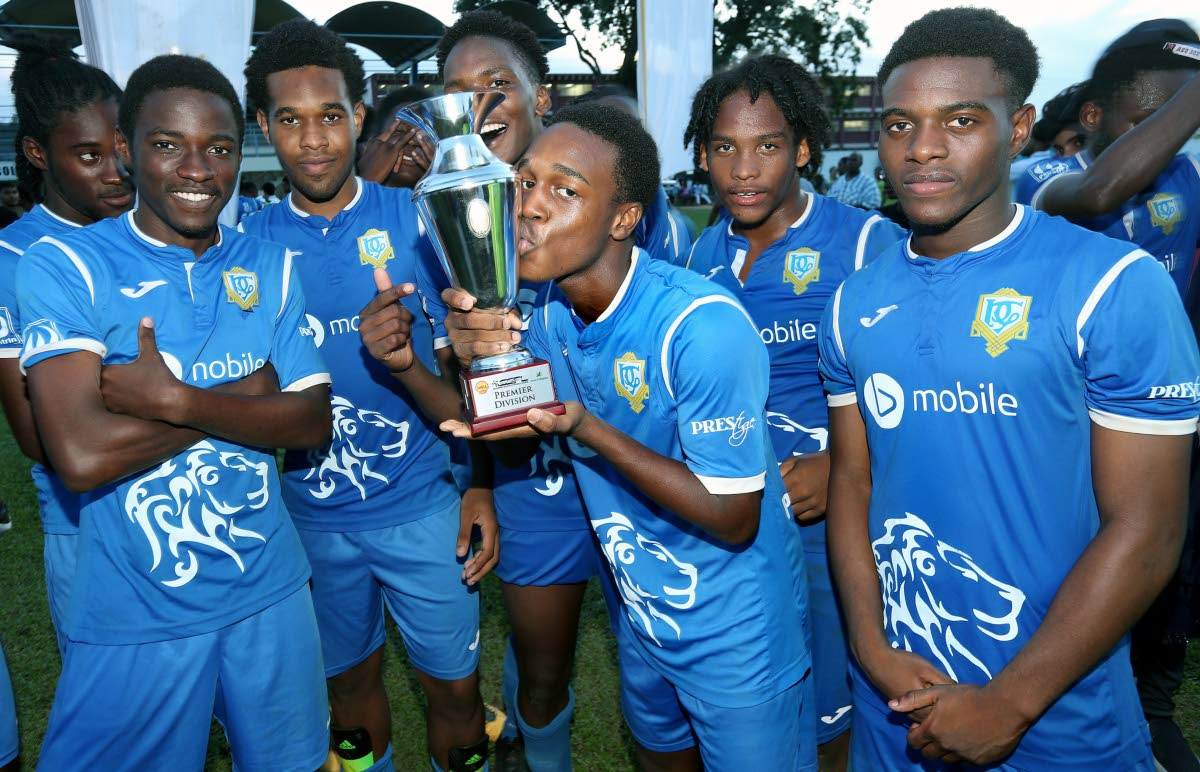 A member of Presentation San Fernando football team kisses the SSFL Premier Division trophy while some of his teammates share their joy after yesterday's success.