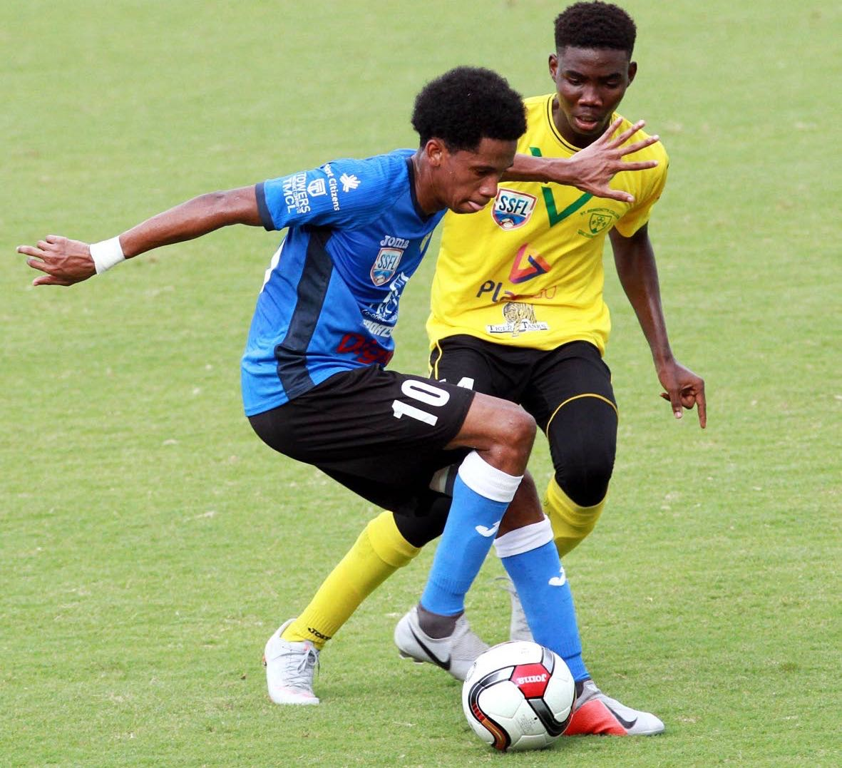 At left, Jordan Riley of Presentation College, San Fernando and Kareem Phillip of St. Benedict's College battle for the ball during an SSFL match, which took place yesterday, at Mannie Ramjohn Stadium, Marabella.