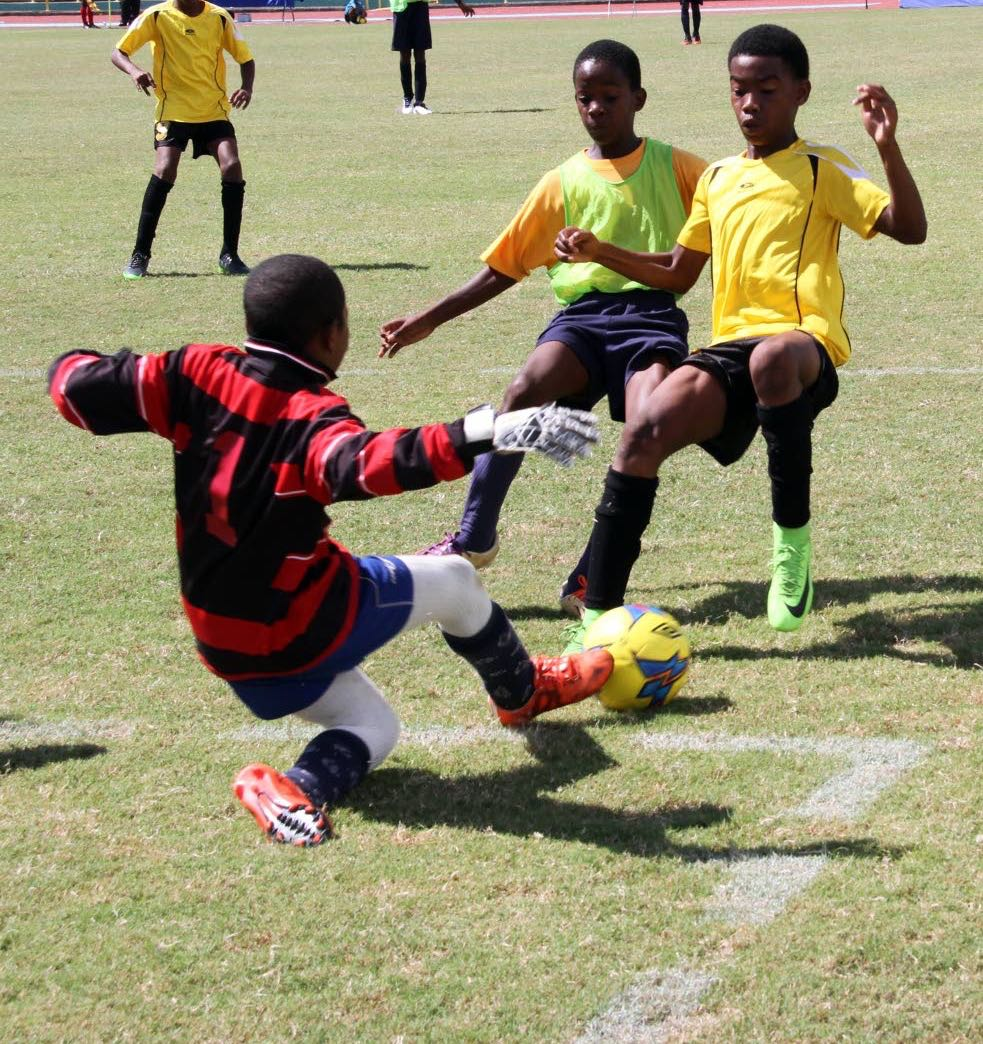 Eastern Boys' goalkeeper, Abdullah Noel makes a tremendous save from a shot by La Pastora player Jadiel Joseph,right during the teams' U12 match in the Atlantic Primary Schools' League finals at Hasely Crawford Stadium yesterday. La Pastora won 2-0.