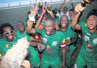 San Juan North's captain Renaldo Boyce celebrates with the Intercol East Zone Champion's Trophy and the rest of his team mates, following their 2 nil victory over Valencia Secondary at the Larry Gomes Stadium, Arima, yesterday.