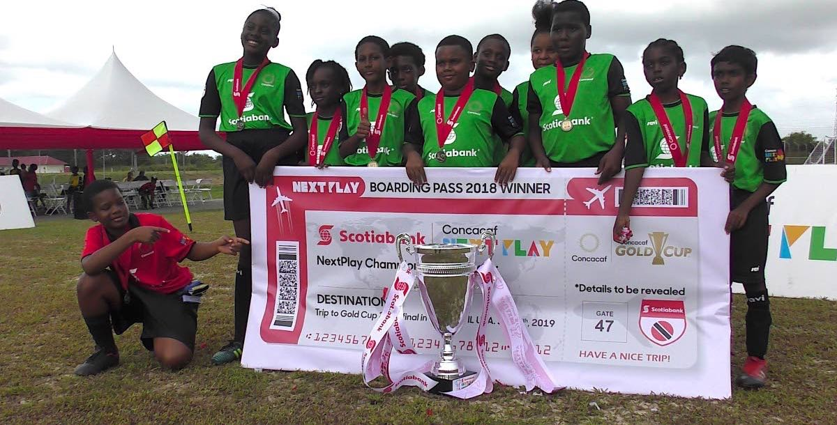 Members of the Siparia Boys RC with a couple girl representatives pose after capturing the CONCACAF NextPlay Cup yesterday.