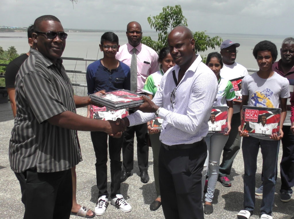 SSFL President William Wallace presents a copy of the Legacy of the Soca Warriors to St Benedict's College head coach and former national player Leonson Lewis.