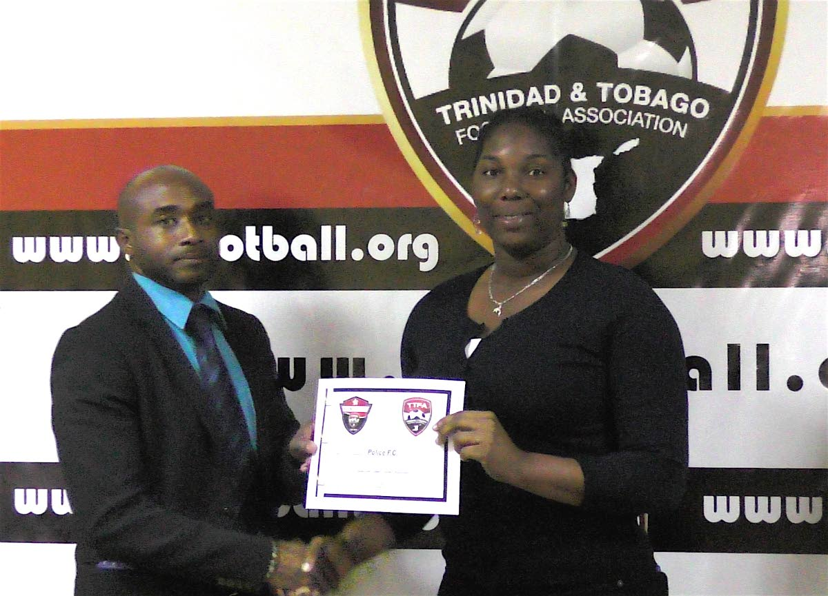 Christophe Braithwate, left, presents a club licensing certificate to a member of the Police FC management team.