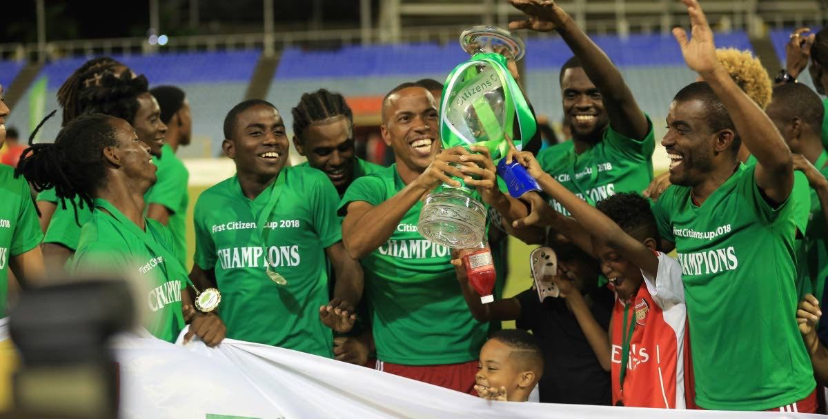 Central FC captain Densill Theobald, centre, lifts the First Citizens Cup trophy as teammates celebrate around him after Friday's final vs Defence Force at the Hasely Crawford Stadium, Mucurapo.