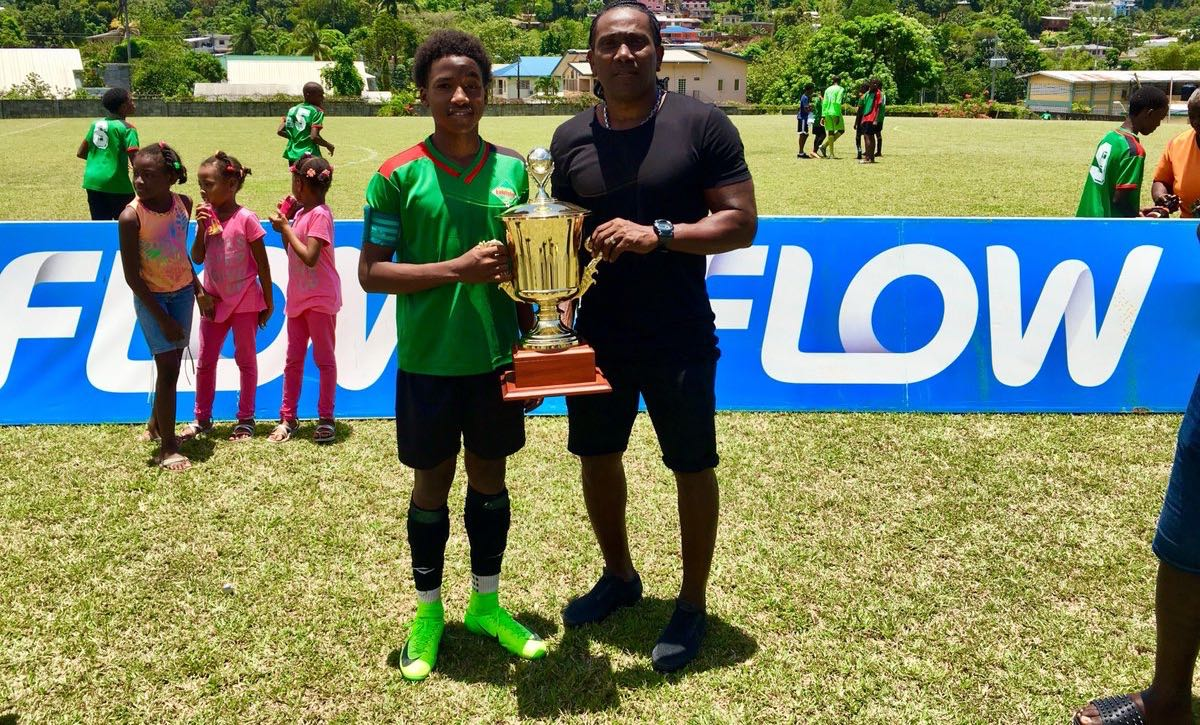 Jaheim Faustin, left, San Juan Jabloteh Under-14 forward and 2018 Flow Youth Pro League Golden Boot winner (12 goals), and his father, former T&T standout Marvin Faustin, pose with the 2018 FYPL U14 trophy at San Juan North Secondary on April 22.