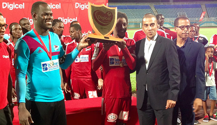 Photo: Central FC goalkeeper and captain Jan-Michael Williams, left, and veteran midfielder Marvin Oliver take centre stage to receive the 2015 Digicel Charity Shield from aspiring FIFA president David Nakhid, third from left, and TT Pro League CEO Dexter Skeene. Central edged rivals W Connection 1-0 at the Ato Boldon Stadium in Couva on 11 September to take the title.