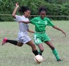 Otisha David from St Augustine tries to evade a challenge from San Juan North player Victoria De Silva. St Augustine won 1-0 with a goal from Khalifa Graham at San Juan North's Ground. Photo: Anthony Harris