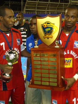 Photo: Caledonia AIA captain Stephan David (left) and Kareem Joseph hold the Lucozade Sport Goal Shield trophy and the CFU Club Championship title is next