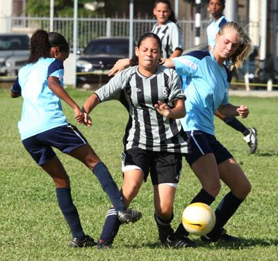 Holy Name's Denise Tucker, centre, is tackled by Providence duo Kennisha Cedeno, left, and Jordan Van Reeken, in the BGTT Secondary Schools' Football League Girls' Championship, on Sunday. Providence won the match 1-0. Photo: Anthony Harris.