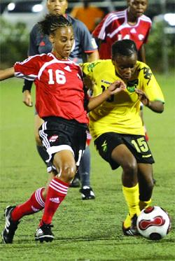 T&T's Kareena Seaton is all out to withstand the challenge of Jamaica's Trudy Carter during their CFU qualifier at the Marvin Lee Stadium last night. The game ended 1-1. Photo: Anthony Harris