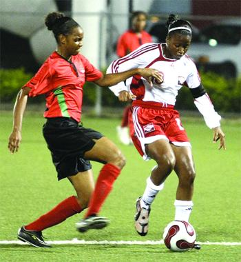 T&T U-20 captain, Mariah Shade, is challenged by St Kitts/Nevis player, Shandor Wilkinson, during the CFU final round qualifier at the Marvin Lee Stadium (MLS), Macoya on Wednesday night. T&T won 6-0, with Shade scoring two goals. Photo: Anthony Harris.
