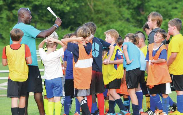 Keita Placide calls out some instruction during a youth soccer camp