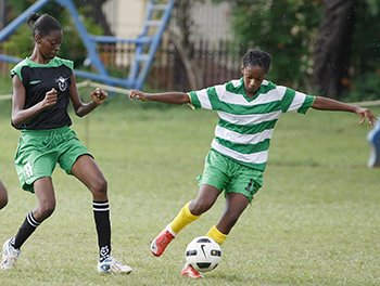 Roxborough midfielder, Kerrisha George (left), battles with St Francois' Astride Joseph during the Big Four clash between the two teams yesterday at QRC. Roxborough won 3-2. Photo: Anthony Harris (Guardian).