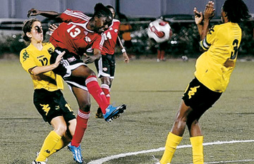 CARIBBEAN CHAMPS: Trinidad and Tobago's Karissa Rodney, second from left, shoots to goal during yesterday's Caribbean Under-20 Women's Football Championship final round tournament clash with Jamaica, at the Marvin Lee Stadium in Macoya. The game ended in a 1-1 draw, and T&T won the title on goal difference. Rodney netted the T&T goal. -Photo: Stephen Doobay.