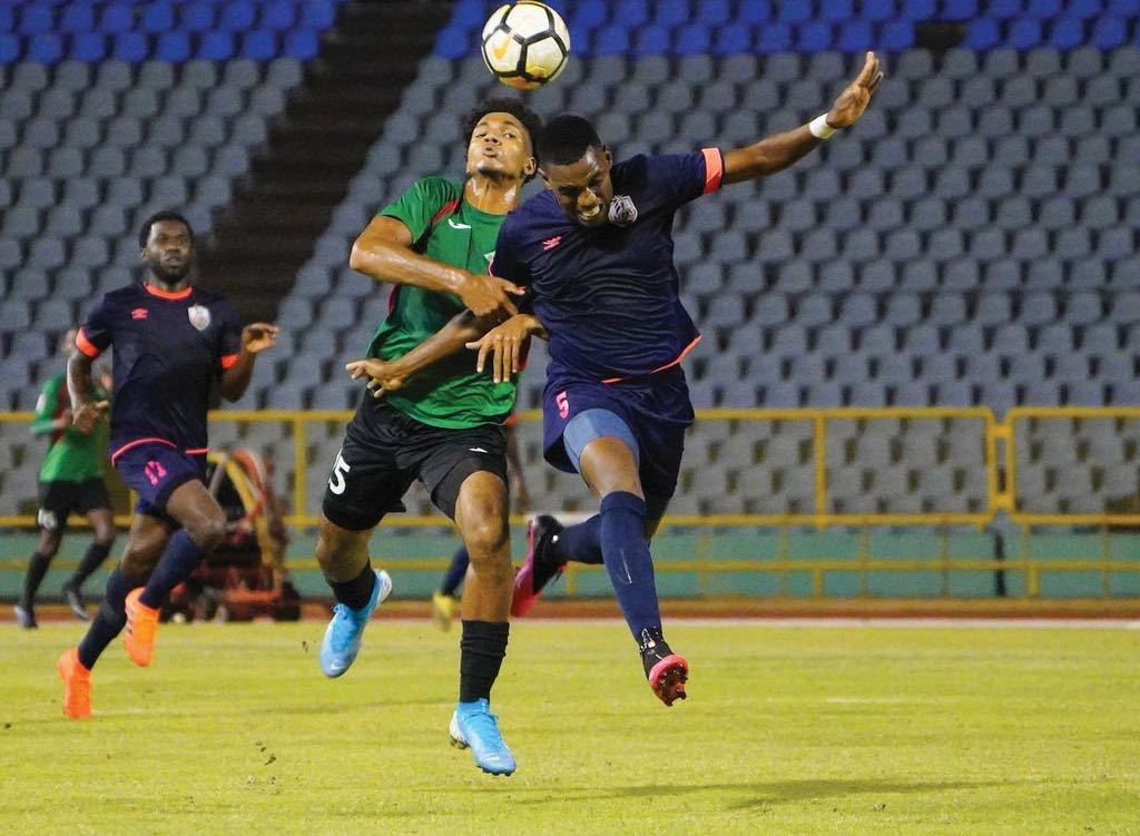 Athletic Club Port-of-Spain defender Seon Thomas, right, vies for the ball with Jabloteh's Justin Wilson during the TT Pro League match between San Juan Jabloteh and Athletic Club Port-of-Spain at the Hasely Crawford Stadium, Port of Spain on Tuesday night. Jabloteh won 1-0.   ...Daniel Prentice/CA-images