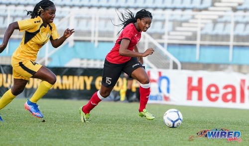Photo: Trinidad and Tobago attacker Afiyah Cornwall (right) tries to get away from Antigua and Barbuda opponent Nicola Stewart during 2020 Olympic qualifying action in Couva on 2 October 2019. (Copyright Daniel Prentice/CA-Images/Wired868)
