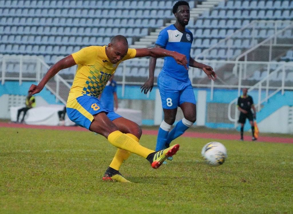 Defence Force Brent Sam, left, hits a shot at goal during the TT Pro League match between Defence Force and Police FC at Ato Boldon Stadium in Balmain, Couva on Sunday. Sam scored two goals to see Defence Force FC get passed Police FC 4-1.  Daniel Prentice/CA-images