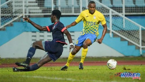 Photo: Defence Force attacker Reon Moore (left) dribbles past AC PoS defender Jokiah Leacock during Pro League action at the Ato Boldon Stadium on 14 February 2020. (Copyright Daniel Prentice/Wired868)