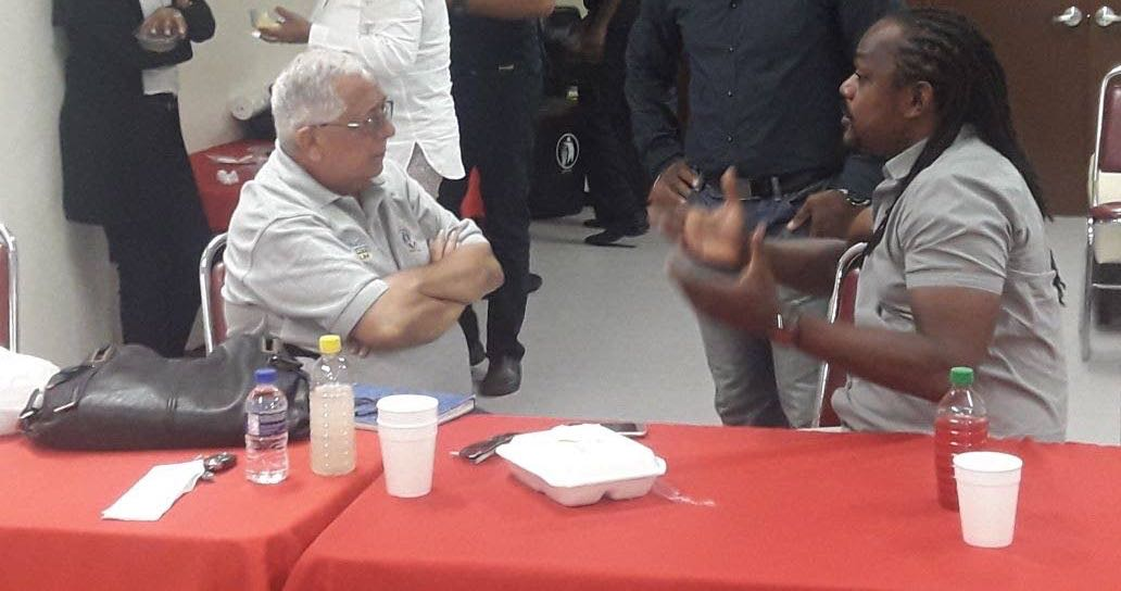 Richard Fakoory, left, listens to Central FC owner Brent Sancho during last week's UEFA/T&T Pro League seminar.