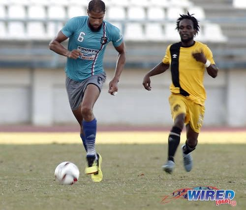 Photo: Morvant Caledonia AIA defender Radanfah Abu Bakr (left) advances with the ball while Cunupia FC flanker Hakeem Legall watches on during Ascension action at the Larry Gomes Stadium on 14 September 2019. (Copyright Annalicia Caruth/Wired868)