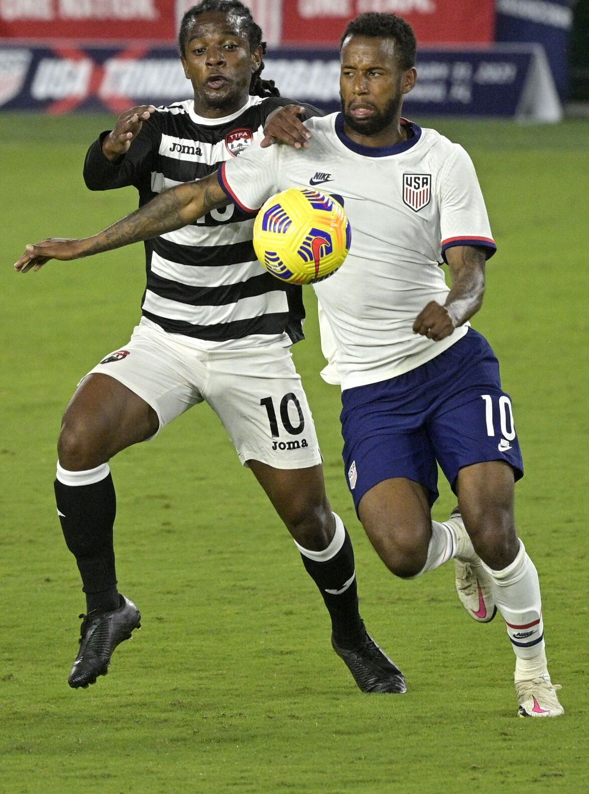 Photo: Trinidad and Tobago midfielder Duane Muckette (left) competes with USA midfielder Kellyn Acosta for the ball during international friendly action in Orlando on 31 January 2021. ...(Copyright AP Photo/Phelan M Ebenhack)