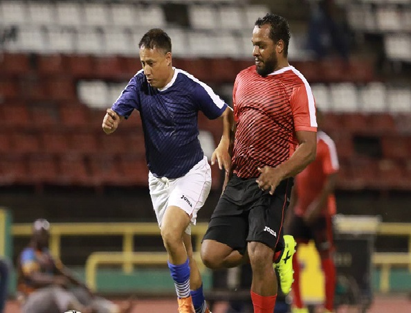 Commissioner of Police Gary Griffith (left), of Team Relief, tries to run past an opponent during the 'Football For a Cause' match at the Hasely Crawford Stadium,Mucurapo, on Friday night.
