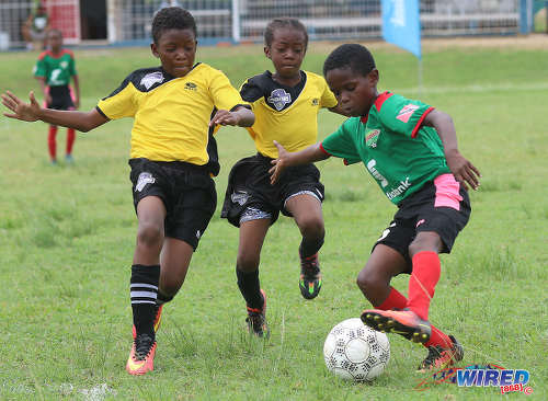 Photo: San Juan Jabloteh's Raheem Mohan (right) tries to elude two Cunupia Extreme players during RBNYL Under-11 action at Constantine Park in Macoya on 10 June 2017. Jabloteh won 2-0. (Courtesy Sean Morrison/Wired868)