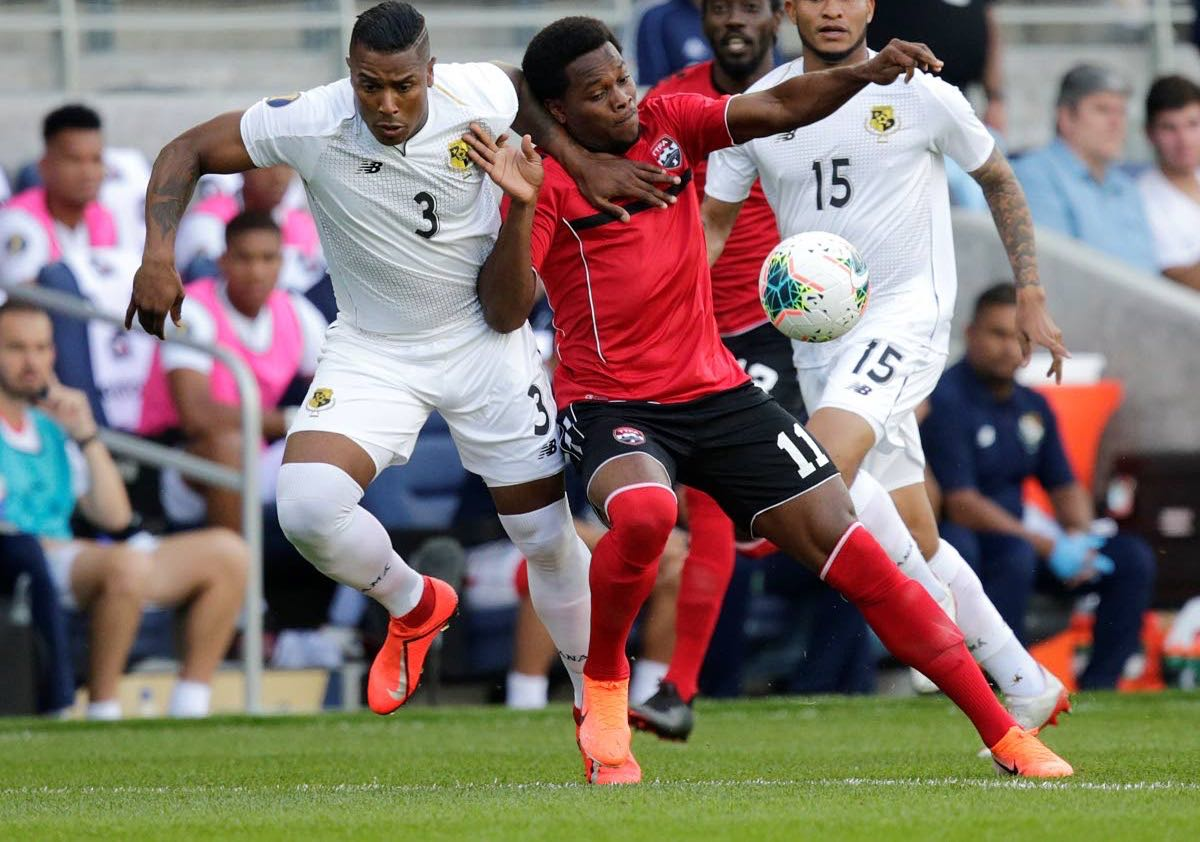 Trinidad and Tobago's Levi Garcia (#11) battles for the ball with Panama's Harold Cummings (left) during the first half of Tuesday's match. (AP PHOTO)