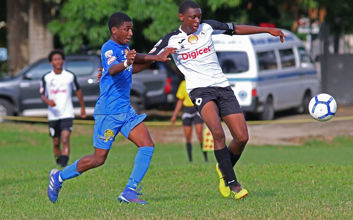 These secondary school footballers, who represent Naparima College (blue) and St Agustine (white), vie for the ball in their SSFL match,at Lewis St, San Fernando,yesterday.