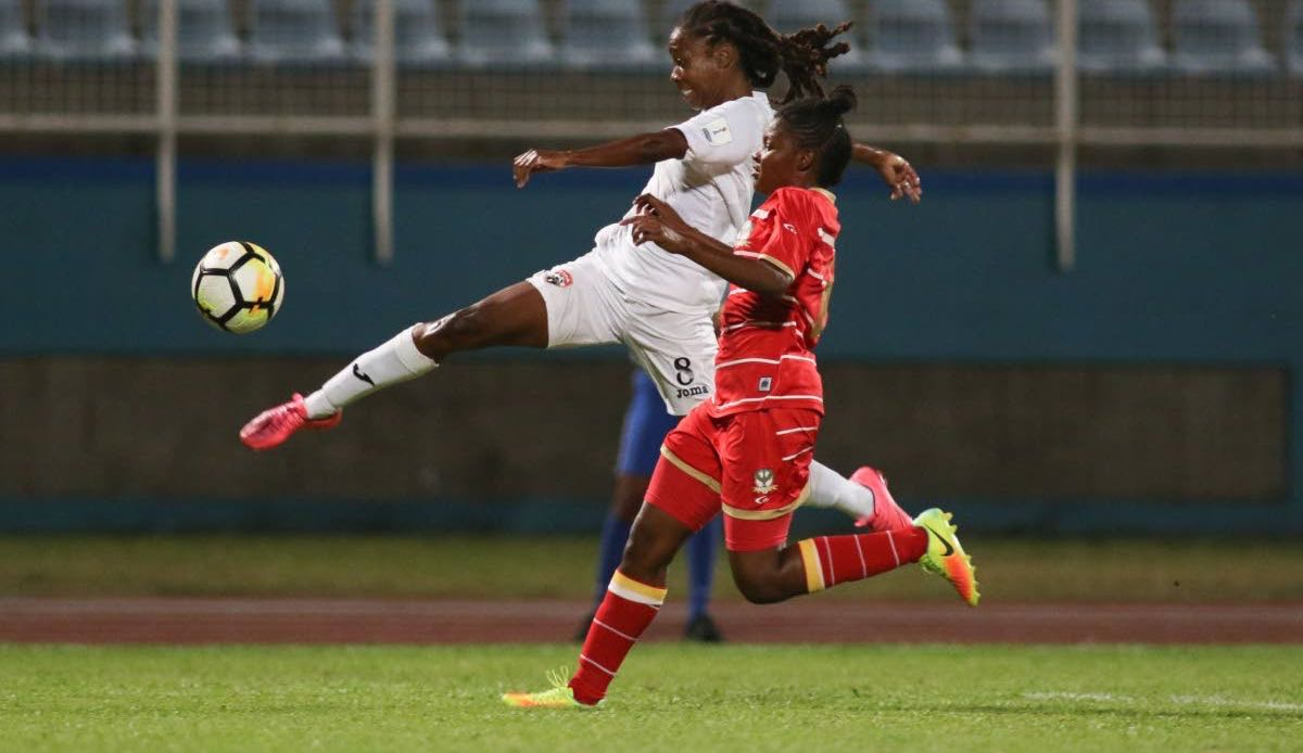 T&T's Patrice Superville goes airborne to make a cross against St Kitts and Nevis in a CONCACAF Women's Championship Qualification match at the Ato Boldon Stadium, Couva, yesterday.