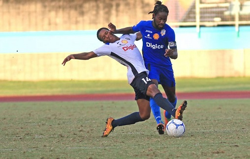 Presentation College's Barclay Aleem (R) vies for control of the ball with Queen's Royal College's Miguel Cross (L),yesterday,during the Secondary Schools Football League match,at the Manny Ramjohn Stadium,Marabella. - MARVIN HAMILTON