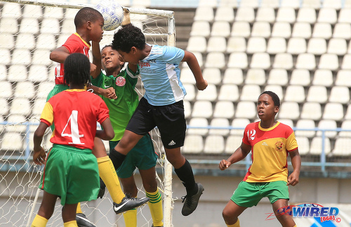 Photo: Trendsetter Hawks goalkeeper Shamael O'Brian (centre) intervenes to thwart QPCC attacker Luca Simon-Thompson (second from right) during RBYL U-11 semifinal action at the Larry Gomes Stadium on 29 June 2019. (Copyright Allan V Crane/CA-images/All Sport)