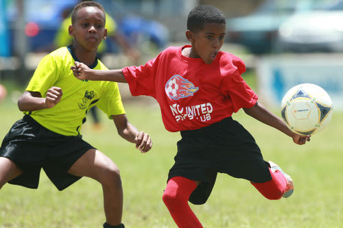 Photo: A Pinto United SC player (right) prepares to strike the ball, despite the attentions of an Adrenaline FA opponent, during Republic Bank National Youth League East Zone Under-12 action on 4 June 2016. Pinto won 4-0. ...(Courtesy Allan V Crane/CAI Sports/All Sport)