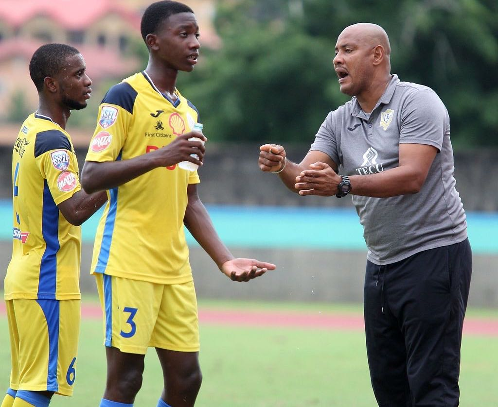 Shawn Cooper, right, the head coach of Presentation College of San Fernando gives instruction to his players Luke Charles, centre, and Zion Allen during their SSFL Premiership Division match at the Ato Boldon Stadium in Balmain, Couva on October 9. Presentation won 1-0.  ANTHONY HARRIS