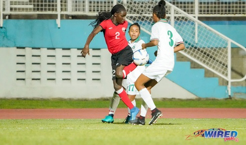 Photo: Trinidad and Tobago defender J'elecia Alexander (left) tries to escape from two Suriname opponents during CFU Challenge Series action at Couva on 27 October 2019. (Copyright Daniel Prentice/CA-Images/Wired868)