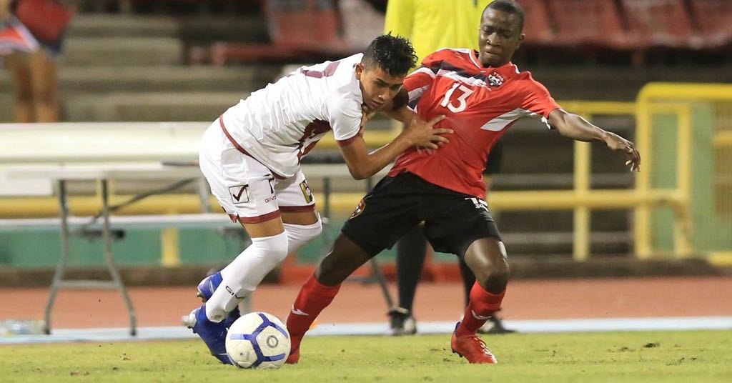 T&T's Kassidy Davidson, right, is held off by Venezuela's Klinsmann Gomez (#7), during the TTFA Boys Under-15 Invitational Tournament between T&T and Venezuela at the Hasely Crawford Stadium, Mucurapo on Friday night. ...Allan V. Crane