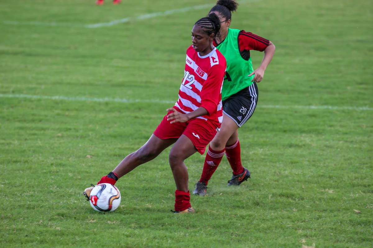 UTT's Tracy Smith,left, dribbles past a Central Women player, during the TT Women's Football League match, at UTT O'Meara, on Saturday. UTT won the match 20-0.